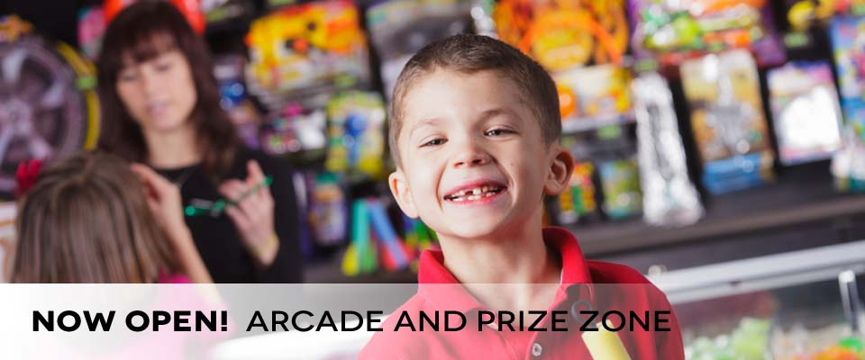 Young boy smiling by prize counter