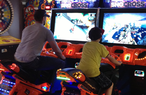 Father and son playing arcade motocross